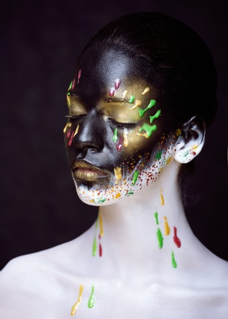 woman with creative make up closeup like drops of colors, facepaint
