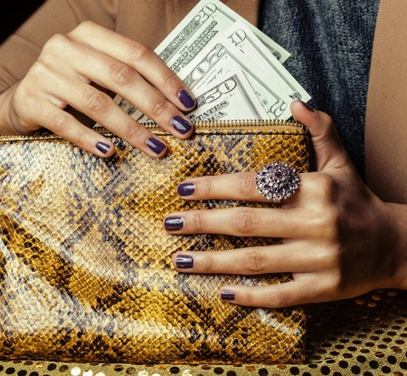 pretty fingers of african american woman holding money close up with purse, luxury jewellery on python clutch, cash for gifts manicure