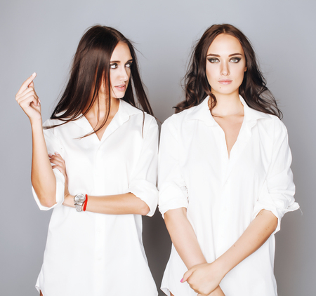 Photo pour two sisters twins posing, making photo selfie, dressed same white shirt, diverse hairstyle friends - image libre de droit