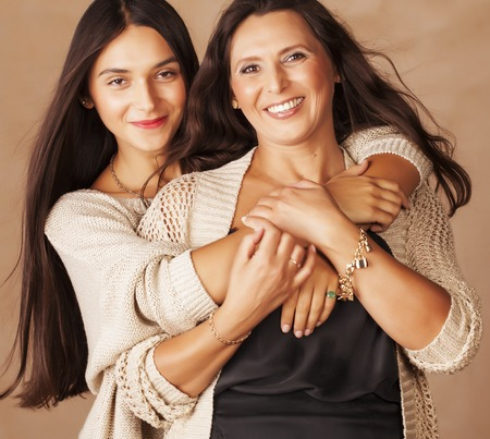Photo for cute pretty teen daughter with mature mother hugging, fashion style brunette makeup close up tann mulattos together, warm colors - Royalty Free Image