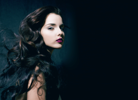 beauty young brunette woman with curly flying hair, femme fatal