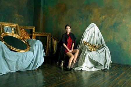 beauty rich brunette woman in luxury interior near empty frames.