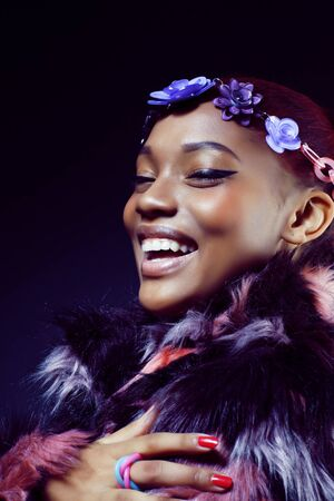 Photo pour young pretty african american woman in spotted fur coat and flow - image libre de droit