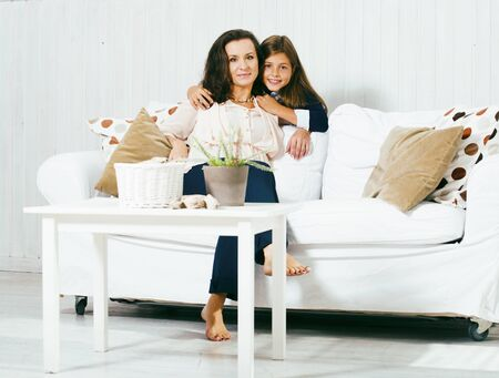 Portrait of smiling young mother and daughter at home, happy fam