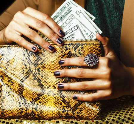 Photo pour pretty fingers of african american woman holding money close up with purse, luxury jewellery on python clutch, cash for gifts - image libre de droit