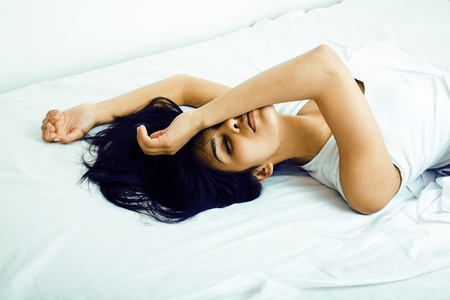 Photo for young pretty tann woman in bed among white sheets having fun, trying to sleep, fooling around - Royalty Free Image