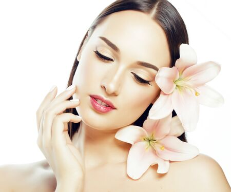 Photo pour young attractive lady close up with hands on face isolated flower lily brunette spa nude makeup macro - image libre de droit