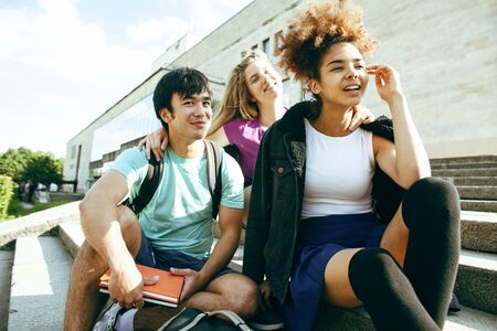 Photo pour cute group of teenages at the building of university with books huggings, diversity nations students lifestyle - image libre de droit