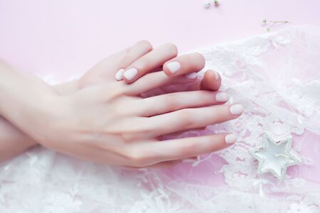 Photo pour woman hands with manicure among white lace on pink background, cosmetic concept - image libre de droit