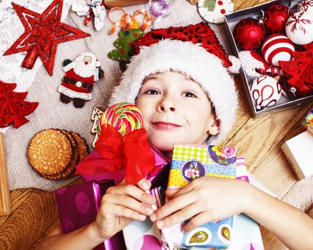 Photo pour little cute boy with Christmas gifts at home. close up emotional happy smiling in mess with toys, lifestyle holiday real people concept - image libre de droit