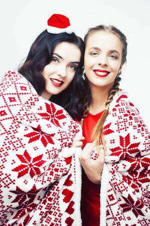 Photo pour young pretty happy smiling blond and brunette woman girlfriends in Santas red hat and Christmas decorated blanket isolated on white background, holiday people concept - image libre de droit
