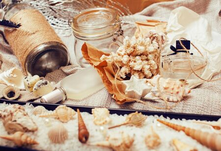 Photo pour a lot of sea theme in mess like shells, candles, perfume, girl stuff on linen, pretty textured post card view vintage close up - image libre de droit