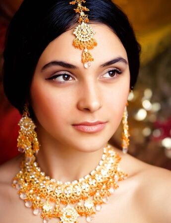 Photo pour beauty sweet real indian girl in sari smiling on black background, jewelry shining - image libre de droit
