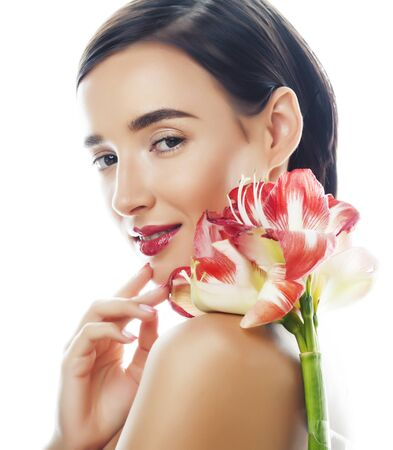 Photo pour young pretty brunette woman with red flower amaryllis close up isolated on white background. Fancy fashion makeup, bright lipstick, creative Ombre manicured nails. spa skin care - image libre de droit