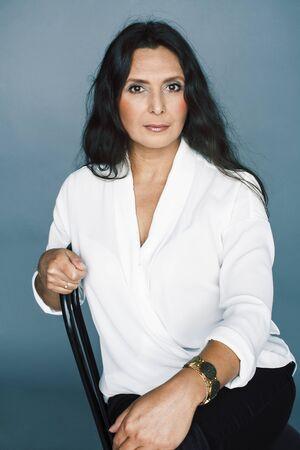 Photo pour pretty brunette confident mature woman sitting on chair in studio, lifestyle people concept - image libre de droit