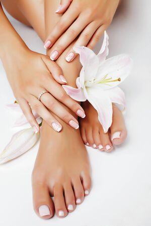 Photo pour manicure pedicure with flower lily closeup isolated on white background perfect shape hands spa salon - image libre de droit