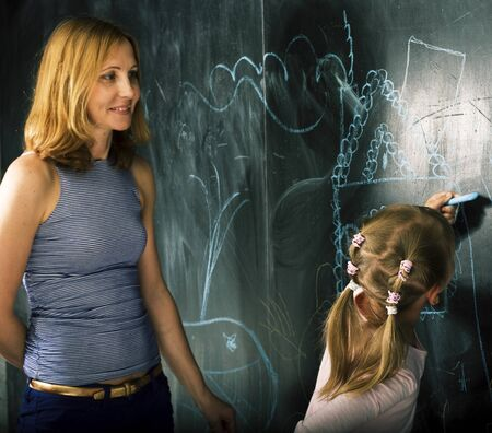 Foto de young teacher with little gitl pupil painting on blackboard, self education mother with daughter together at self-isolation, lifestyle people concept - Imagen libre de derechos