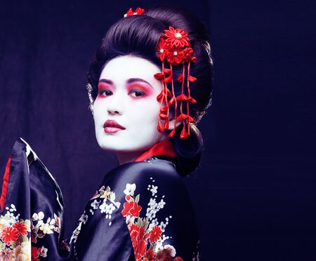 Photo for young pretty real geisha in kimono with sakura and decoration on black background - Royalty Free Image