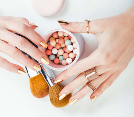Photo pour woman hands with golden manicure and many rings holding brushes, makeup artist stuff stylish, pure closeup pink flower rose among cosmetic for makeup - image libre de droit