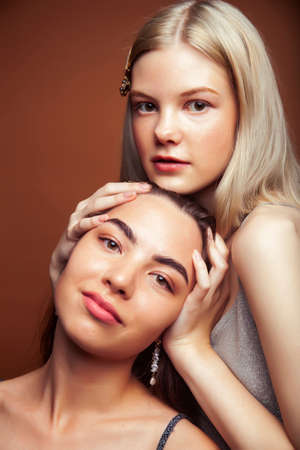 Photo for two pretty diverse girls happy posing together: blond and brunette on brown background, lifestyle people concept - Royalty Free Image