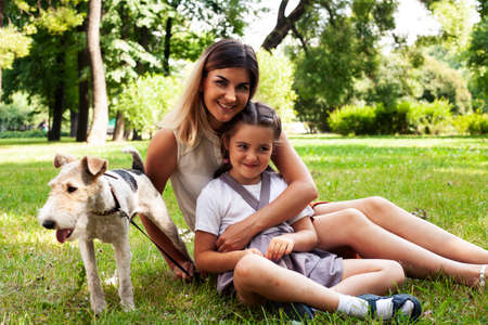 Photo pour young pretty caucasian mother walking with little cute daughter and dog fox terrier, lifestyle people concept - image libre de droit