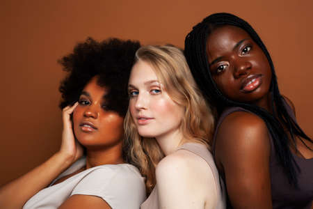 Photo for young pretty african and caucasian women posing cheerful together on brown background, lifestyle diverse nationality people concept - Royalty Free Image