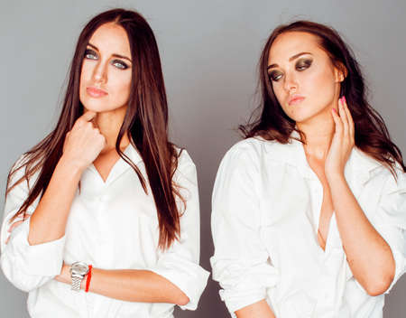 Photo pour two sisters twins posing, making photo selfie, dressed same white shirt, diverse hairstyle friends, lifestyle people concept - image libre de droit