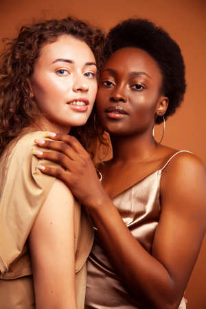 Photo for two pretty girls african and caucasian blond posing cheerful together on brown background, ethnicity diverse lifestyle people concept - Royalty Free Image