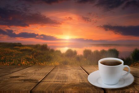 Photo pour Coffee cup on wood table and view of beautiful sunset or sunrise background - image libre de droit