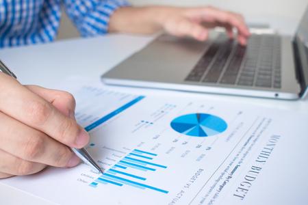 Foto de Close-up image of the hand of a business worker pointing graph with a pen on a modern white desk. - Imagen libre de derechos