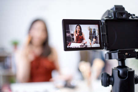 Photo for The camera is recording a video, a beautiful Asian blogger teaching you how to use makeup in the room. - Royalty Free Image