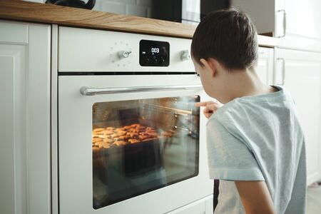 Photo pour A young boy cooks cookies and patiently waiting next to a safe oven in the home interior. - image libre de droit