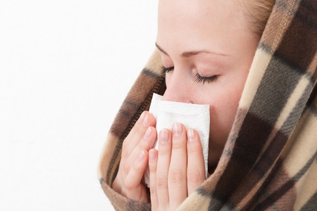 A woman with a symptoms cold flu allergy wiping or blowing her nose