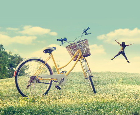 Bicycle on the white flower field and grass in sunshine nature background, Pastel and vintage color tone