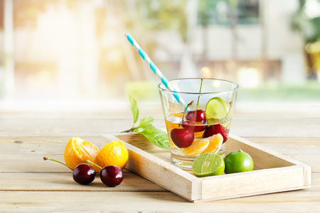 Foto de healthy detox water, glass of cherry, orange and lime on wooden tray garden background - Imagen libre de derechos