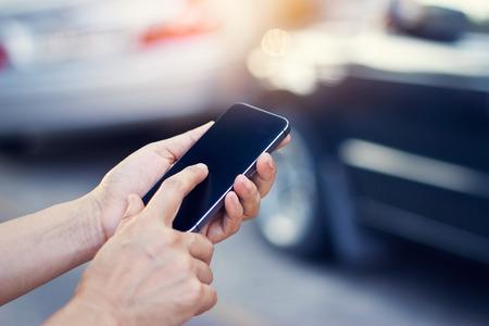Photo pour woman using smartphone at roadside after traffic accident, soft focus - image libre de droit