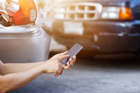 Photo pour Man using smartphone at roadside after traffic accident - image libre de droit