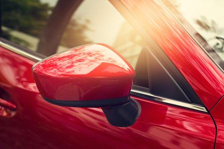 Foto de side rear-view mirror red car on street background - Imagen libre de derechos