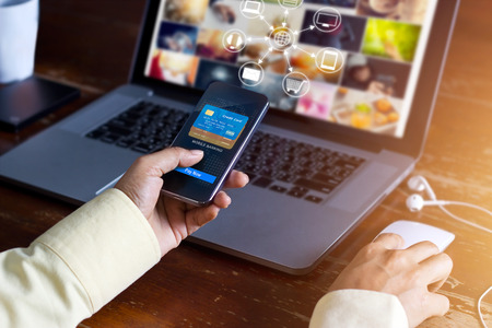 Foto de Man using mobile payments online shopping and icon customer network connection on screen, m-banking and omni channel - Imagen libre de derechos