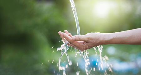 Photo for Water pouring in woman hand on nature background, environment issues - Royalty Free Image