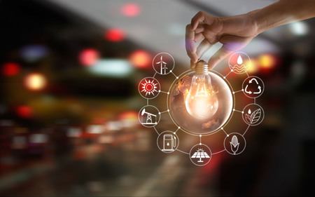 Photo for Hand holding light bulb in front of global show the world's consumtion with icons energy sources for renewable, sustainable development. Ecology and enviroment concept. Elements of this image furnished by NASA. - Royalty Free Image