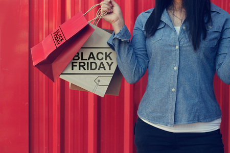 Woman holding Black Friday shopping bag while standing on red metal wall the mall background