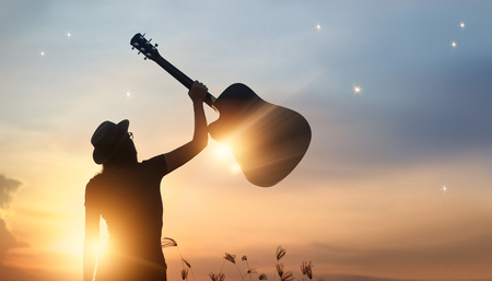 Foto de Musician holding guitar in hand of silhouette on sunset nature background - Imagen libre de derechos