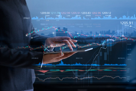 Photo pour Business people checking stock market on tablet and analysing financial data on a screen with graph and candlestick chart on LED monitor virtual on the city background - image libre de droit