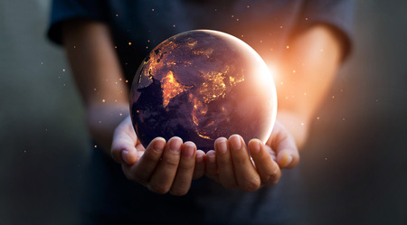Foto de Earth at night was holding in human hands. Earth day. Energy saving concept - Imagen libre de derechos