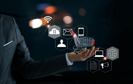 Businessman with shopping cart in hand and icons customer network connection. Digital marketing and shopping online. Business and payment concept