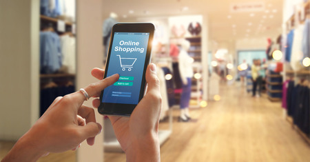 Photo pour Smart phone online shopping in woman hand. Network connection on mobile screen. Payments online. Shopping mall department store background - image libre de droit
