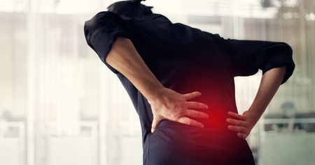 Man suffering from back pain cause of office syndrome, his hands touching on lower back. Medical and heathcare concept