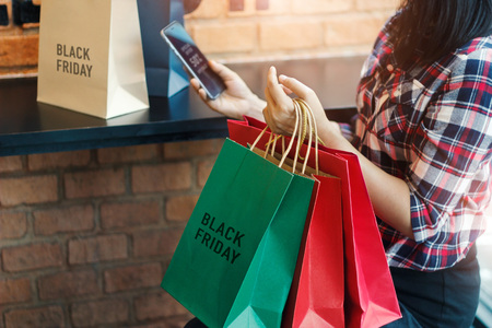 Foto für Black Friday, Woman using smartphone and holding shopping bag while sitting in the mall background - Lizenzfreies Bild