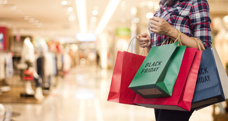 Photo pour Black Friday, Woman holding many shopping bags while walking in the shopping mall background. - image libre de droit